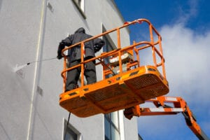Man on lift power washing building exterior